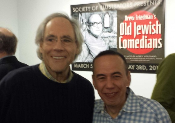 Comedians Robert Klein and Gilbert Gottfried in front of the Old Jewish Comedians Banner featuring Friedman's illustration of the late great Jack Benny.